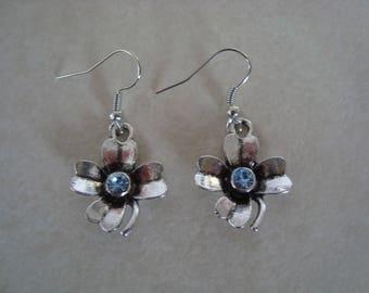 Silver metal flower and blue rhinestone earrings