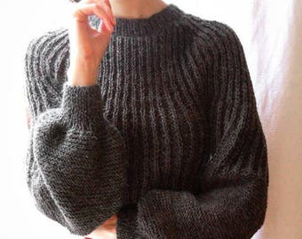 Handmade knitted and little fuzzy sweater with very large sleeves.
