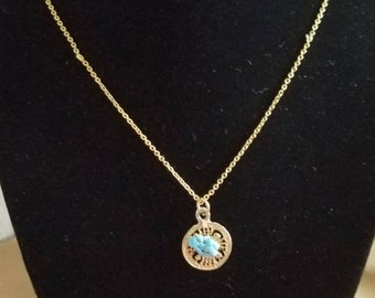 Turquoise-like nugget on gold tone circle necklace.