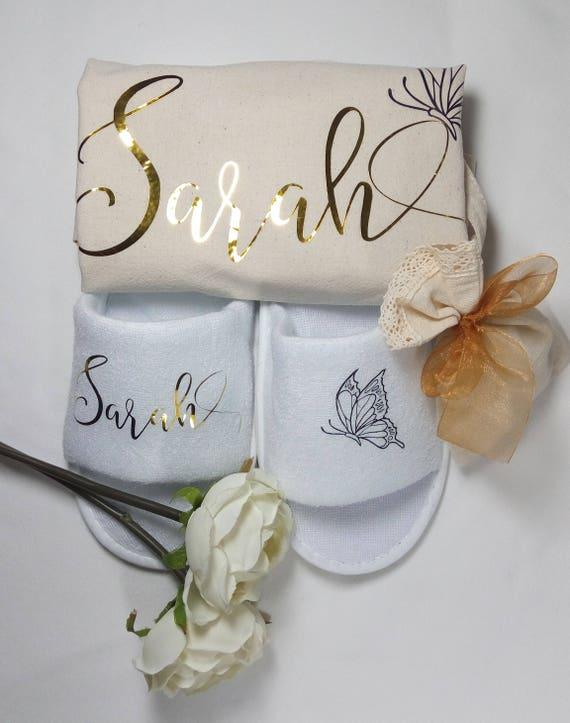 """[Image description: A pair of white slippers and a cream tote bag with the name """"Sarah"""" written in modern calligraphy. A white rose lies next to them.]"""