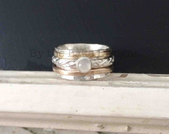 spinner ring,  3 tone with with a moonstone on the center band