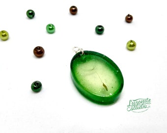 Oval pendant with a dandelion seed embedded inside, with a green halo, handmade