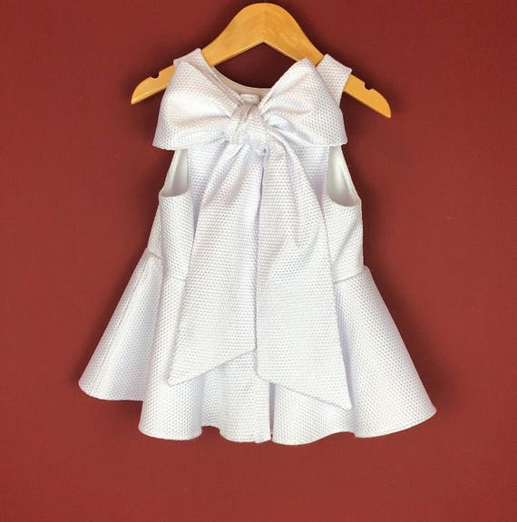 "The ""Bow-Backed Peplum"" in White Pique."