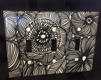 Black and white floral triple switch plate cover.