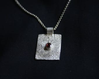 Textured silver pendant featuring faceted garnet