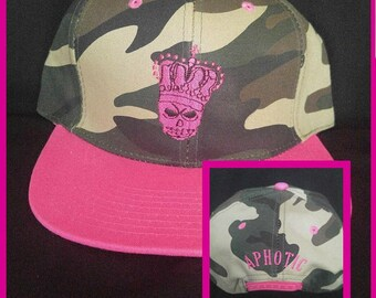 Camouflage and Pink (Brim) Hat with Pink Skull/Crown on the Front and 'Aphotic' on the Back.