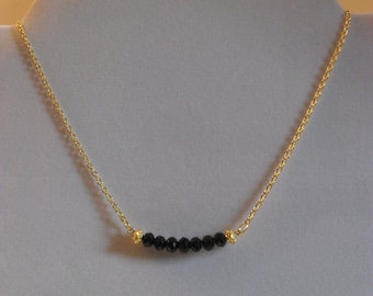 Sophisticated black faceted rondelle and gold-plated filigree bar necklace