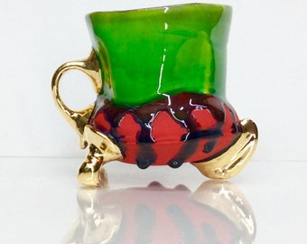 green and red drippy glaze mug with gold and one finger handle