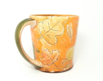 Orange fall leaf themed Earthenware mug. Wheel thrown, food safe leafy mug made by Kaitlyn Brennan