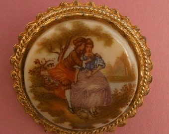 B652) A lovely vintage gold tone metal cameo glass lovers circular brooch