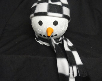 A adorable light up snow person with a black and white checker fleece hat and scarf