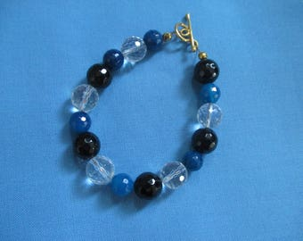 A bracelet with blue, black and clear quartz  and gold plated clasp.