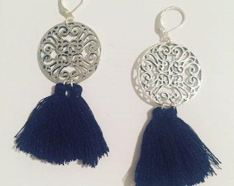 Ornate dangling earrings of two black tassels