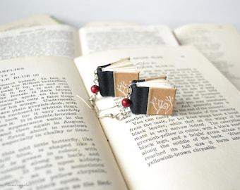 Orecchini a forma di libro con fiori di tarassaco e perla di legno rossa. Libro nero in miniarura disegnato e cucito a mano.