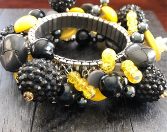The Sting - cha cha style stretch bracelet with new and repurposed beads and buttons in blacks, grays and yellows; stainless steel base