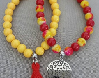 Yellow and red hand-made By Freyja Creations beaded bracelet duo. Red acrylic Pompom and mandala stainless steel charm.