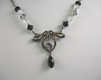 Necklace with vintage stamping and Swarovski crystals,gunmetal finish, black and crystal