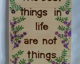 The best things in life are not things wood burned  and painted plaque with purple flowers, embellished with colored crystals.