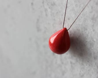 Red handmade ceramic tear drop necklace on gray silk cord