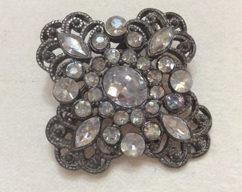 Vintage 1950s pot metal rhinestone hurricane brooch pin.