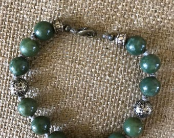 Green beaded bracelet.  Nice green beads  on knotted hemp with bronze accents.  9""
