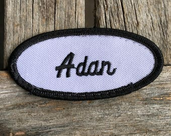 """Adan. A white work shirt patch that says """"Adan"""" in black script with black border"""