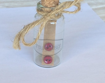 Tiny Button Stud Earrings, displayed in glass bottle