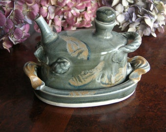 Wheel thrown and altered stone ware oil bottle with tray.