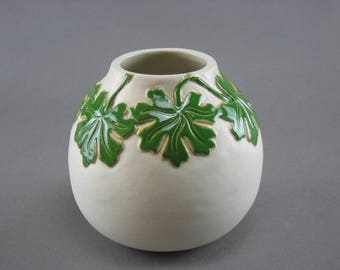 White vessel with geranium leaves