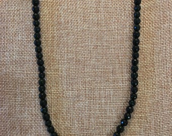 This is dark green sand stone strung on cotton cord