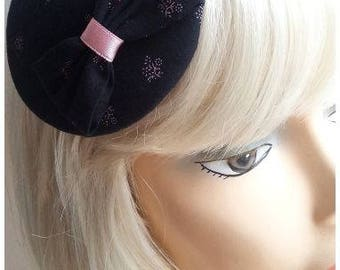 Tiny black hat, little headpiece with flowers.
