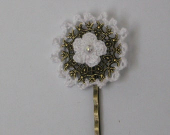 Metal bronze bobby pin with crochet white lace around and white knitted flower in the middle