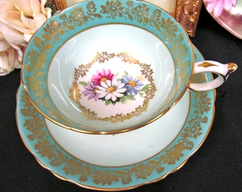 Paragon tea cup and saucer blue and gold gilt floral daisy wide mouth teacup