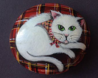 Hand painted pebble cat on tartan cushion.