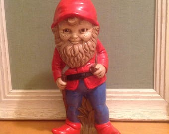 Garden gnome, satchel, walking stick and pipe, full beard, smiling, red hooded jacket, red boots, blue pants.