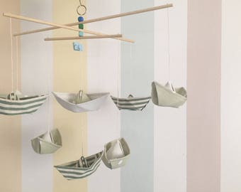 Mobile Montessori with cloth boats, lift their eyes and look at the sea