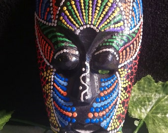 A solid wooden handcarved, brightly painted tribal mask.