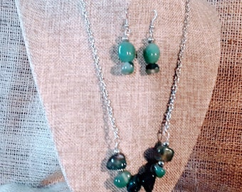 Silver Wire Wrapped Green Sea-Glass Pendant necklace with various hues of green gemstones. Earrings of coordinated gemstones.