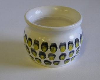 White wheel thrown pot with a Black and Yellow dot pattern