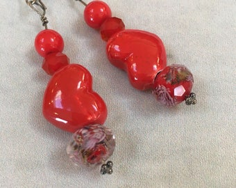 Red ceramic heartshaped earrings with sikver dangle ear wires .