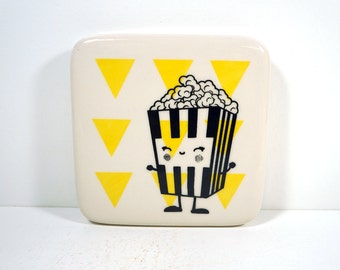 tile with a happy popcorn dude on yellow triangles. Made to Order / Pick Your Colour