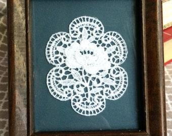 Vintahe framed rose doily - wooden frame matted against blue background
