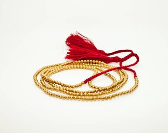 Gold Bead Wraparound Bracelet with Warm Red Tassel
