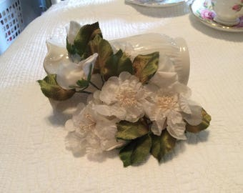 Vintage spray of cream flowers with green leaves