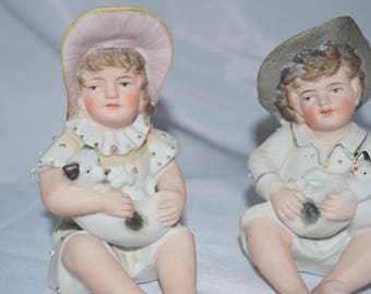 German Porcelain Bisque Piano Baby Pair Two Statues Figurines Boy Holding Kitty Cat Girl Holding Puppy Dog Heubach Quality