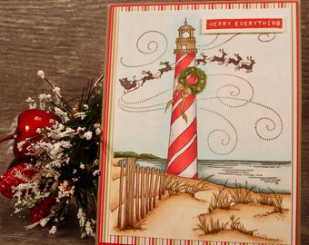 Merry Everything Card, hand made holiday card with Santa and reindeers behind a candy cane lighthouse on the beach, hand stamped and colored