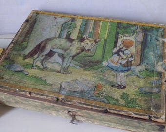 Old vintage wooden puzzle with Grimm's fairy tales images in wooden box shabby