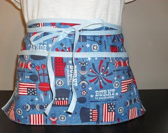Utility/waitress/vendor apron with 3 pockets.  Blue background with American themed BBQ and the words 'burnt to perfection'.