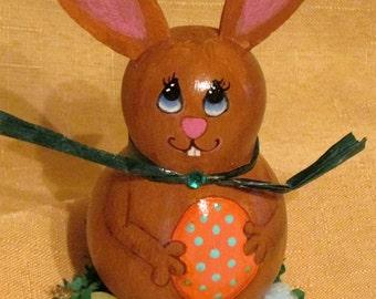 Brown Easter Bunny Gourd holding orange egg