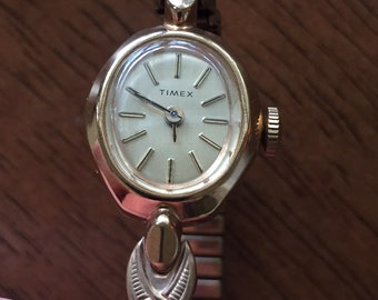 Vintage Timex Ladies gold plated mechanical wind watch gold hands silver oval dial 18mm diameter running well c 1960s